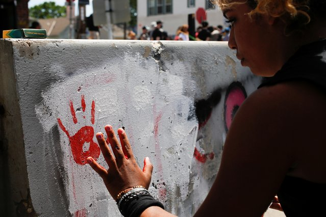 A woman who calls herself E paints the newly-moved barricades after city employees began to reopen George Floyd Square, the area where George Floyd was killed in Minneapolis police custody the year before, in Minneapolis, Minnesota, U.S., June 3, 2021. (Photo by Nicole Neri/Reuters)