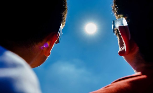 Pupils of primary school IBS Ababil, look at the solar eclipse with special glasses, in Schiedam, The Netherlands, 10 June 2021. For the first time since 2015, a partial solar eclipse can be seen again, with the sun partly obscured by the moon. (Photo by Marco de Swart/EPA/EFE)