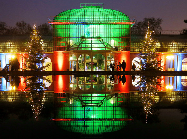 "The main building is reflected in a fountain in the Palmgarten (palm garden) during the exhibition ""Winter Lights"" where buildings, trees and lakes are illuminated in Frankfurt, Germany, Saturday, December 17, 2016. (Photo by Michael Probst/AP Photo)"