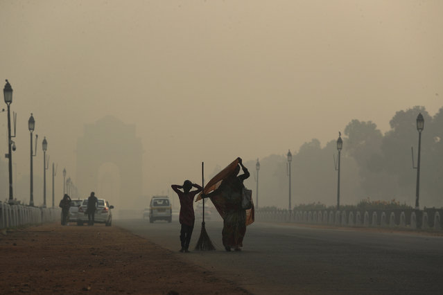 A municipal worker with her daughter leaves after sweeping the India Gate area as a thick lawyer of pollution haze hangs a day after Diwali festival, in New Delhi, India, Thursday, November 8, 2018. Toxic smog shrouds the Indian capital as air quality falls to hazardous levels with tens of thousands of people setting off massive firecrackers to celebrate the major Hindu festival of Diwali on Wednesday night. (Photo by Manish Swarup/AP Photo)