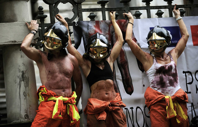 Firefighters, with their bodies covered in fake blood, take part in a protest to demand better working conditions outside regional parliament in Oviedo, northern Spain, January 28, 2016. (Photo by Eloy Alonso/Reuters)