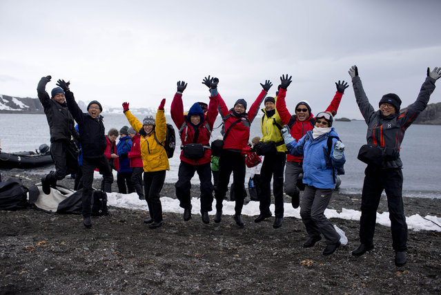 In this February 2, 2015 photo, tourists jump as they pose for a picture, after disembarking from the Ocean Nova cruise ship, on King George Island, Antarctica. This tourist season, which runs November through March, more than 37,000 visitors are expected to walk on the coldest continent on Earth, about 10 percent more than the year before. (Photo by Natacha Pisarenko/AP Photo)
