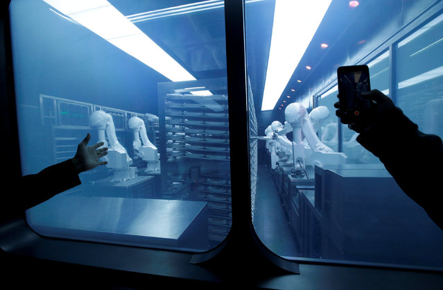 A customer takes a picture as robotic arms collect pre-packaged dishes from a cold storage, done according to the diners' orders, at Haidilao's new artificial intelligence hotpot restaurant in Beijing, China, November 14, 2018. (Photo by Jason Lee/Reuters)