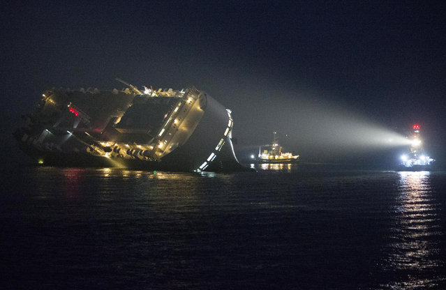 A tug illumnates the cargo ship Hoegh Osaka as it lies on its side after running aground in the Solent estuary, near Southampton in southern England, January 4, 2015. (Photo by Peter Nicholls/Reuters)