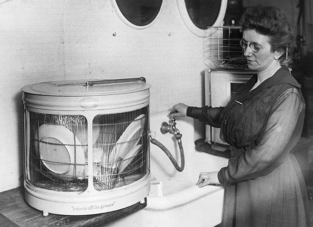 """All the drugery of dishwashing in this three-times -a day task, which comes to the house wife who does her own house work, has been eliminated by the new dish washer shown in the photograph on April 25, 1921. It is the invention of a Cincinnati school teacher, who sought to make things a bit more pleasant for his wife. Incedently, his idea was worth 12,00 to him, for a manufacturing concern thought so much of the """"dish-washer"""" they purchased the rights and will seek to add a little joy to thousands of other housewives. With the aid of only hot water, dishes placed in a wire rack and set into the drum are made clean and spotless in two minutes. (Photo by Bettmann Archive/Getty Images)"""