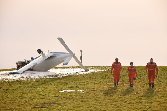 Australia's State Emergency Service (SES) personnel gather at the scene of a light plane crash near the Capital Golf Course, in Melbourne, Australia, 22 June 2021. A pilot was injured and rushed to hospital after his light plane crashed shortly after taking off from Moorabbin Airport. (Photo by James Ross/EPA/EFE)