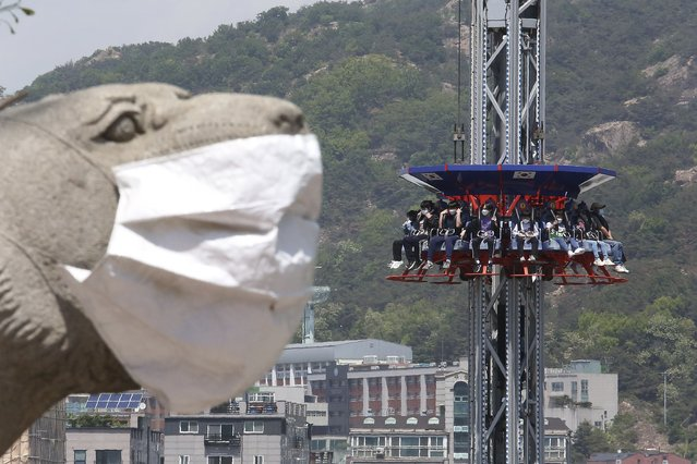 People wearing face masks as a precaution against the coronavirus ride Gyro Drop as they visit to celebrate Children's Day at Children's Grand Park in Seoul, South Korea, Wednesday, May 5, 2021. (Photo by Ahn Young-joon/AP Photo)