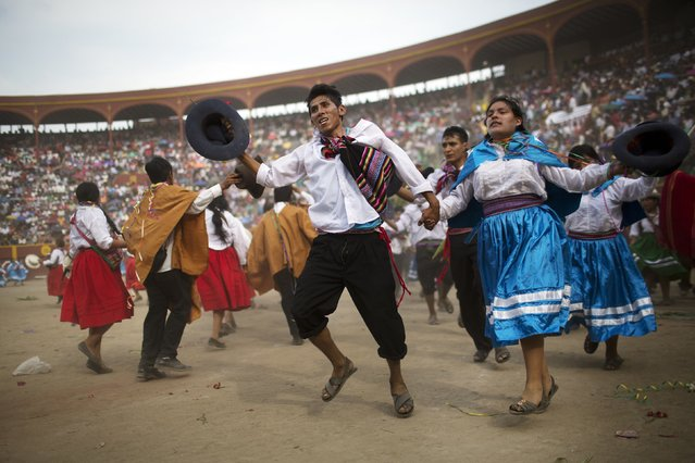 In this Sunday, March 29, 2015 photo, people perform a traditional dance during the Vencedores de Ayacucho dance festival, in the Acho bullring, in Lima, Peru. (Photo by Rodrigo Abd/AP Photo)