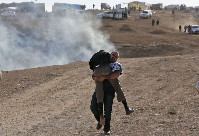 A Palestinian activist carries a wounded man during clashes following a demonstration against the construction of Jewish settlements in the village of Ein al-Beida, north of the city of Nablus in the West Bank, on November 17, 2016. (Photo by Abbas Momani/AFP Photo)