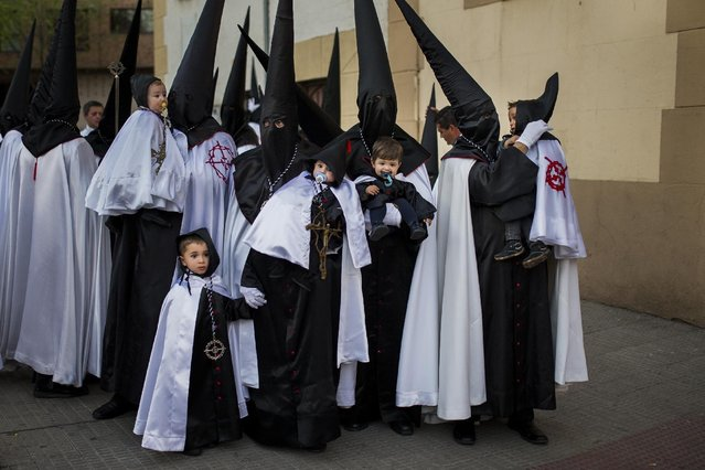 """Penitents from """"Jesus en su Tercera Caida"""" brotherhood and their children take part in a procession in Zamora, Spain, Monday, March 30, 2015. Hundreds of processions take place throughout Spain during the Easter Holy Week. (Photo by Andres Kudacki)/AP Photo)"""