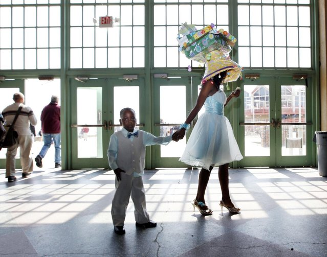 Esonni Hall, of Neptune, N.J., wears a homemade Easter bonnet as she walks with her brother Georandy Johnson before judging of decorated Easter outfits during Asbury Park's 80th annual Easter Parade on Sunday, April 5, 2015, in Asbury Park, N.J. (Photo by Mel Evans/AP Photo)