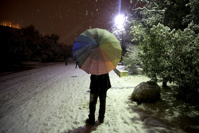 A man holds his umbrella during snowfall on the Areopagitou pedestrian street beneath the Acropolis hill during snowfall in Athens, Greece, January 10, 2017. (Photo by Alkis Konstantinidis/Reuters)