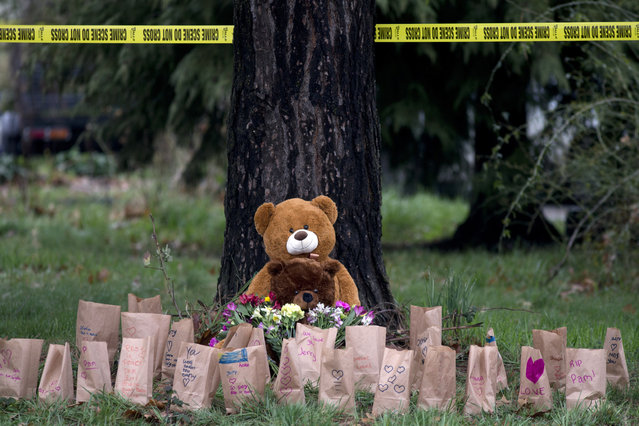 Crime scene tape marks off an area, Monday, January 21, 2019, near a memorial of candles, flowers and teddy bears outside a house where authorities say a man killed four members of his family, including his infant daughter, at the Canby, Oregon, home they shared, over the weekend. (Photo by Beth Nakamura/The Oregonian via AP Photo)