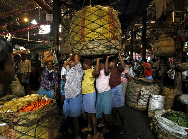 Workers carry a packed basket of vegetables at a wholesale vegetable market in Kolkata in this February 27, 2015 file photo. (Photo by Rupak De Chowdhuri/Reuters)