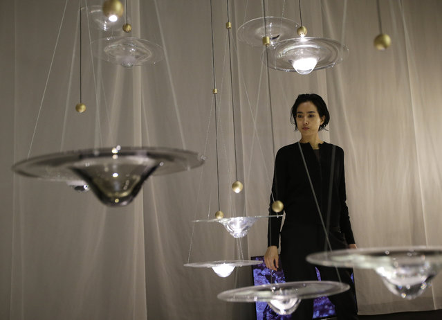 In this picture taken on Tuesday, April 14, 2015, designer Nao Tamura walks past her installations at the Milan Furniture Fair, in Milan, Italy. (Photo by Antonio Calanni/AP Photo)