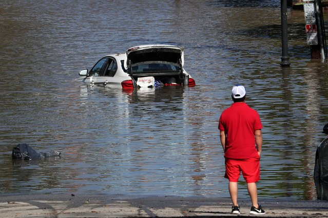 A man looks at a car in floodwaters after remnants of Ida brought drenching rain, flash floods and tornadoes to parts of the Northeast in Mamaroneck, New York, September 2, 2021. (Photo by Mike Segar/Reuters)