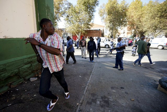 An African immigrant runs as a police officer holds a gun to disperse them in Johannesburg, April 17, 2015. South African police fired rubber bullets and a stun grenade on Friday to disperse a gang of African immigrants who had armed themselves with machetes in a run-down district of east Johannesburg, a Reuters photographer said. (Photo by Siphiwe Sibeko/Reuters)