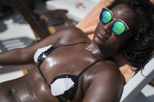 In this January 11, 2017 photo, a woman in search of crisp tan lines lounges in the sun wearing a bikini made of black electrical tape at the Erika Bronze rooftop salon in the suburb of Realengo in Rio de Janeiro, Brazil. Dermatologists are more horrified than impressed with the technique, which they say can increase the chance of getting skin cancers, including melanoma. (Photo by Renata Brito/AP Photo)