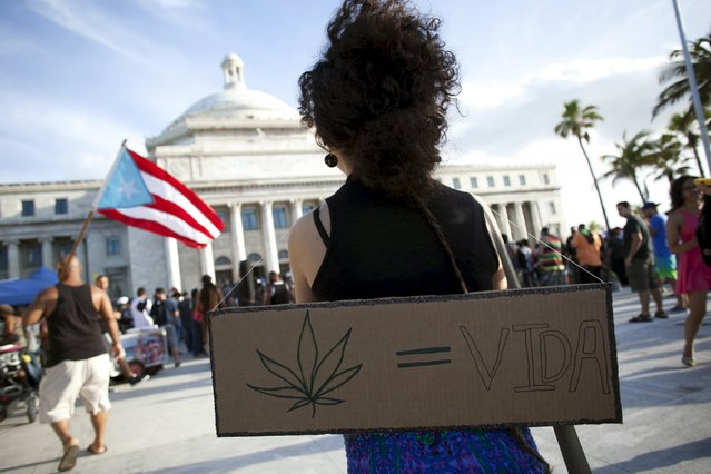 "A demonstrator holds a sign while standing with others during a protest outside the Capitol building in San Juan April 20, 2015. The sign shows a marijuana leaf and the writing ""Life"". (Photo by Alvin Baez/Reuters)"