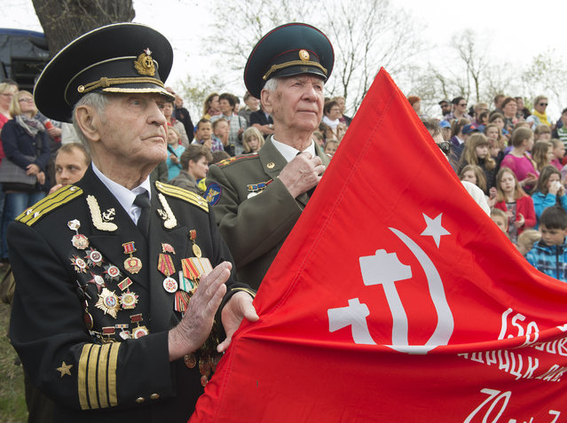 Russian veteran Nikolai Mihalovic Beljajev, 92, left, holds a flag with the emblem of the former Soviet Union during the 70th anniversary celebrations of the so-called Elbe Day in Torgau, eastern Germany, Saturday, April 25, 2015. (Photo by Jens Meyer/AP Photo)