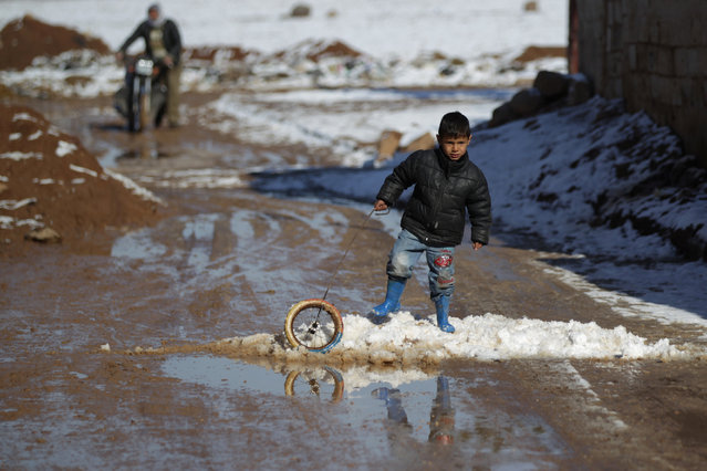 A boy plays with a wheel on snow in al-Rai town, northern Aleppo countryside, Syria January 28, 2017. (Photo by Khalil Ashawi/Reuters)