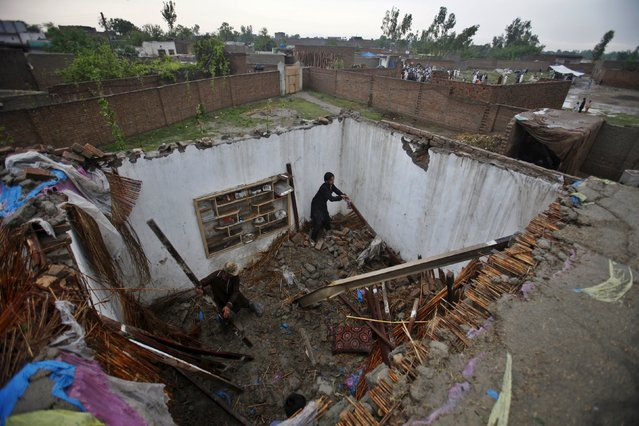 "Men search through the debris of a house partially-destroyed following heavy rain in the outskirts of Peshawar, Pakistan, April 27, 2015. A freak ""mini-cyclone"" tore roofs of buildings and brought down trees and power poles in Pakistan, killing 45 people and injuring more than 200, officials said on Monday. (Photo by Fayaz Aziz/Reuters)"