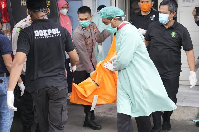 Officers load a body bag containing the body of a victim of a prison fire to be transferred to the national police hospital for identification at the local hospital in Tangerang on the outskirts of Jakarta, Indonesia, Wednesday, September 8, 2021. A massive fire raged through the overcrowded prison early Wednesday, killing a number of inmates. (Photo by Dita Alangkara/AP Photo)