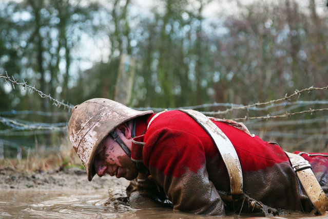 A competitor  crawls under barbed wire during the Tough Guy Challenge on January 26, 2014 in Telford, England.  (Photo by Bryn Lennon/Getty Images)