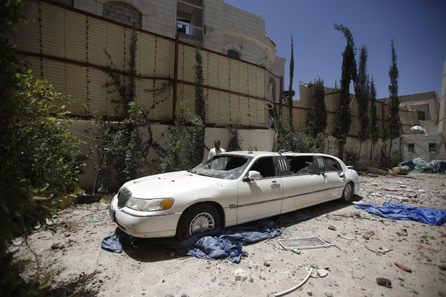 A man looks at his car which, was damaged by a recent Saudi-led airstrike that hit a site that many believe held a large weapons cache in Yemen's capital, Sanaa,  Saturday, April 25, 2015. With combatants fighting in neighborhoods and Saudi-led coalition warplanes pounding Iran-backed rebels from the sky. (Photo by Hani Mohammed/AP Photo)