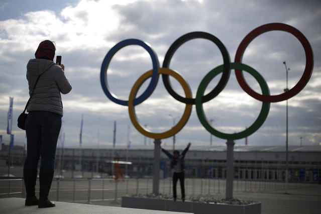 Railway passengers take photos in front of the Olympic Rings at the Olympic Park train station ahead of the upcoming 2014 Winter Olympics, Wednesday, February 5, 2014, in Sochi, Russia. (Photo by David Goldman/AP Photo)