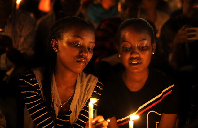 Rwandan women sitting in the stands, hold candles as part of a candlelit vigil during the memorial service held at Amahoro stadium in the capital Kigali, Rwanda, Sunday, April 7, 2019. Rwanda is commemorating the 25th anniversary of when the country descended into an orgy of violence in which some 800,000 Tutsis and moderate Hutus were massacred by the majority Hutu population over a 100-day period in what was the worst genocide in recent history. (Photo by Ben Curtis/AP Photo)