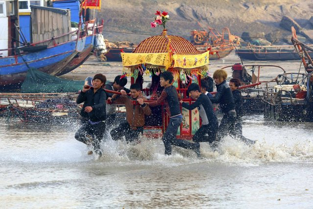 """Villagers run in sea water as they carry a sedan chair holding their gods during an annual folk performance known as """"sea rush"""" to celebrate the Lantern Festival in Nanri Island of Putian, Fujian province, on February 18, 2014. (Photo by Reuters/Stringer)"""