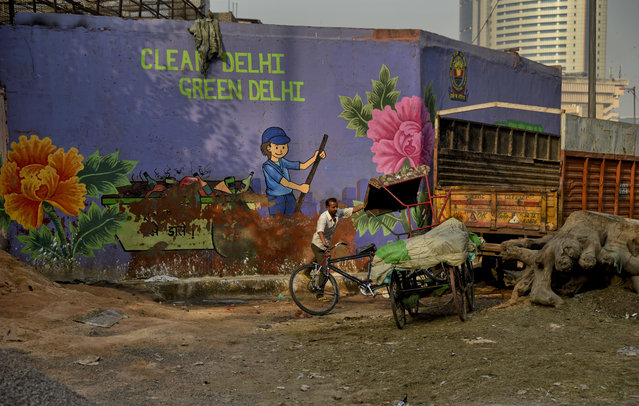 In this October 10, 2018, photo, an Indian cycle rickshaw puller maneuvers his rickshaw past an awareness mural campaigning for a clean and green Delhi in New Delhi, India, Wednesday. Huge sums have been spent on a marketing blitz, including videos of Bollywood stars sweeping the streets, for the government's ambitious Swachh Bharat, or Clean India, program launched by Modi in 2014. (Photo by R.S. Iyer/AP Photo)