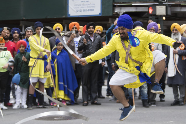 Participants practice Gatka, a martial art, as they march down Madison Avenue during the Sikh Day Parade, celebrating the Sikh holiday of Vaisakhi, Saturday, April 27, 2019, in New York. (Photo by Mary Altaffer/AP Photo)