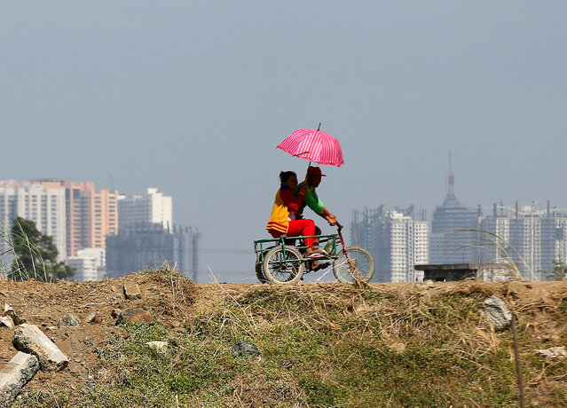 Filipino farmers riding on a three-wheeled bicycle traverse a dried-up portion of a field in Taguig City, south of Manila, Philippines, 15 February 2017. Due to escalating global warming, Filipino farmers complain that their crops being damaged due to deminishing sources of water. (Photo by Francis R. Malasig/EPA)