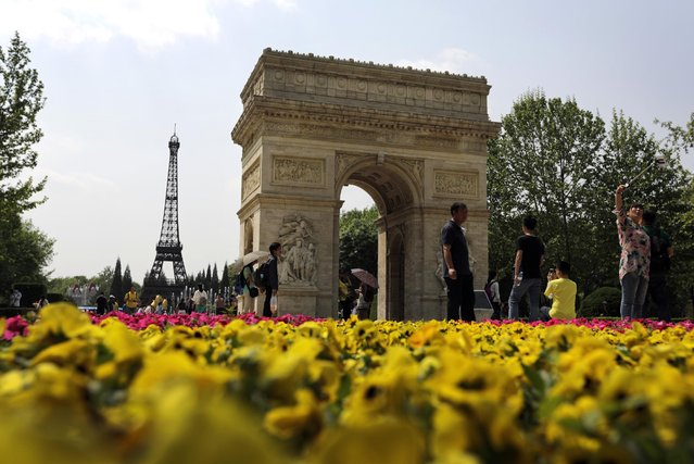 A woman uses a selfie stick to take souvenir photo as visitors tour near the replica of France's Arch of Triumph and Eiffel Tower on display at the World Park in Beijing, China, Saturday, May 2, 2015. (Photo by Andy Wong/AP Photo)
