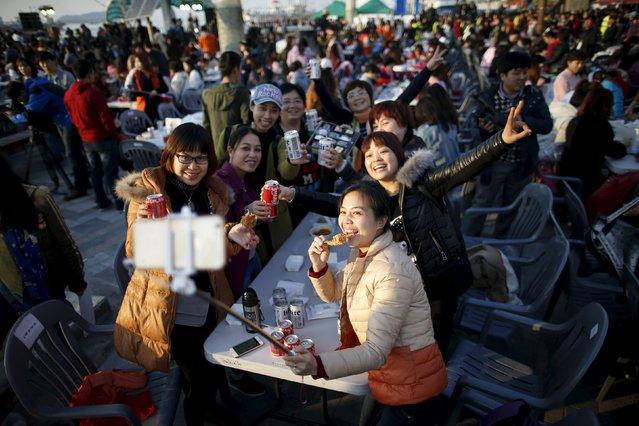 Chinese tourists take a selfie with canned drinks and fried chicken pieces during an event organized by a Chinese company at a park in Incheon, South Korea, March 28, 2016. (Photo by Kim Hong-Ji/Reuters)