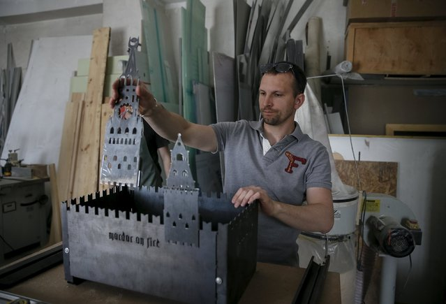 "A Ukrainian artist assembles a barbecue grill in the shape of Moscow's Kremlin at his workshop in Kiev May 14, 2015. A group of Ukrainian artists are working on a project entitled ""Mordor on Fire"" where they create grills that are sold, and some donated to Ukrainian soldiers in the eastern conflict zone. (Photo by Gleb Garanich/Reuters)"