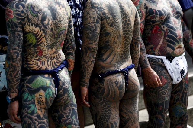 Men show their traditional full body tattoos as they pose outside the Sensoji temple during the Sanja Matsuri festival in the Asakusa district of Tokyo May 17, 2015. (Photo by Thomas Peter/Reuters)