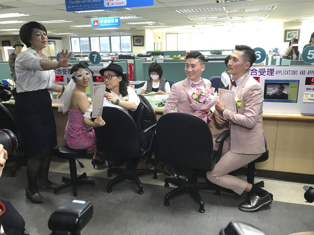 Two same-s*x couples show their legal marriage certificates at the registration office in Xingyi District in Taipei, Taiwan, Friday, May 24, 2019. Hundreds of same-s*x couples in Taiwan are rushing to the household registration office on the first day that a landmark decision to legalize same-s*x marriage has taken effect. (Photo by Johnson Lai/AP Photo)