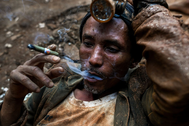 This photo taken on May 16, 2019 shows a miner resting as he smokes a cigar at a ruby mine in Mogok, north of Mandalay. (Photo by Ye Aung Thu/AFP Photo)