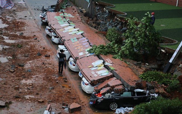 Eleven cars are buried by a fallen wall after a heavy rain at Yichun Huanggang experimental school on May 19, 2019 in Yichun, Jiangxi Province of China. Heavy rain hit Yichun on Sunday. (Photo by Zou Haibin/VCG via Getty Images)