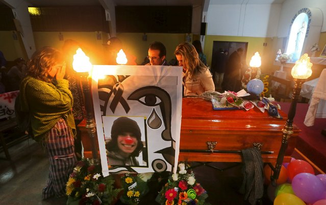 Relatives of Exequiel Borvaran, a student who was shot dead on May 14 following a protest march, attend his wake in a church in Quilpue city, Chile May 15, 2015. Authorities believe Borvaran, 18, and fellow student Diego Guzman, 25, were killed by an irate resident as they sprayed graffiti on the wall of his building. (Photo by Rodrigo Garrido/Reuters)