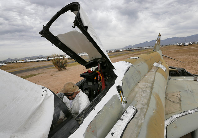 A demilitarization crew member removes components from the cockpit of an F-4 Phantom slated for destruction at the 309th Aerospace Maintenance and Regeneration Group boneyard in Tucson, Ariz. on Thursday, May 21, 2015. The 309th is the United States Air Force's aircraft and missile storage and maintenance facility and provides long and short-term aircraft storage, parts reclamation and disposal. (Photo by Matt York/AP Photo)