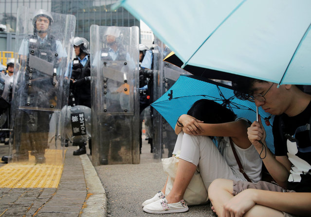 Protesters holding umbrellas occupy a street near a row of police officers outside the Legislative Council building during a demonstration against a proposed extradition bill in Hong Kong, China on June 12, 2019. (Photo by Thomas Peter/Reuters)