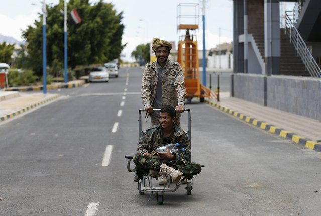 A Houthi militant pushes a comrade on a luggage trolley at the international airport of Yemen's capital Sanaa May 5, 2015. (Photo by Khaled Abdullah/Reuters)