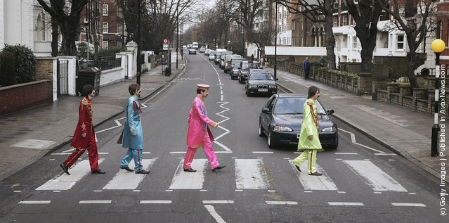 Actors play the part of the Beatles crossing a zebra crossing outside the Abbey Road studios