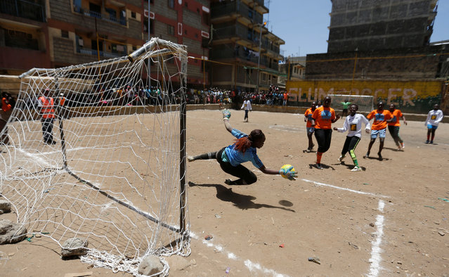A female goalkeeper saves the ball at the Mathare Environmental Conservation Youth Center during a soccer match to celebrate the International Women's day in Nairobi, Kenya, March 8, 2017. (Photo by Thomas Mukoya/Reuters)