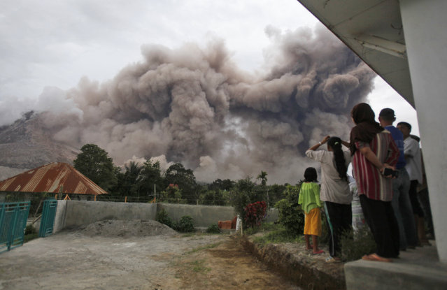 Villagers watch as Mount Sinabung releases pyroclastic flows in Tiga Serangkai, North Sumatra, Indonesia, Saturday, June 13, 2015. The volcano, which was put on it highest alert level last week, has sporadically erupted since 2010 after being dormant for 400 years. (AP Photo/Binsar Bakkara)