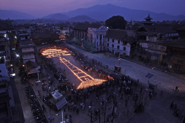 Nepalese people light up candles in the shape of the Dharahara Tower, center and the Kasthamandap temple, top left, which were destroyed in last year's devastating earthquake at the Basantapur Durbar Square in Kathmandu, Nepal, Sunday, April 24, 2016. Nepalese held memorial services to mark the anniversary of the disaster that killed nearly 9,000 people and left millions homeless. (Photo by Niranjan Shrestha/AP Photo)